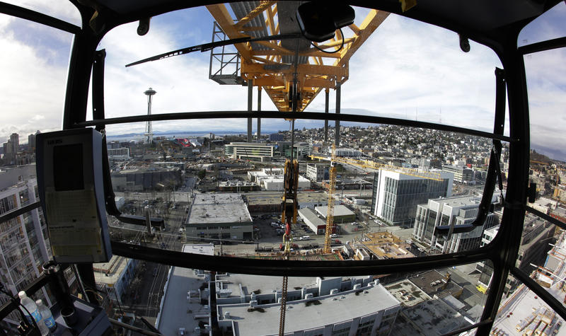 In this Feb. 10, 2015, photo, Seattle's Space Needle and several construction cranes are shown from the operating cab of a 238-foot high construction crane working on a new building in Seattle's South Lake Union neighborhood.