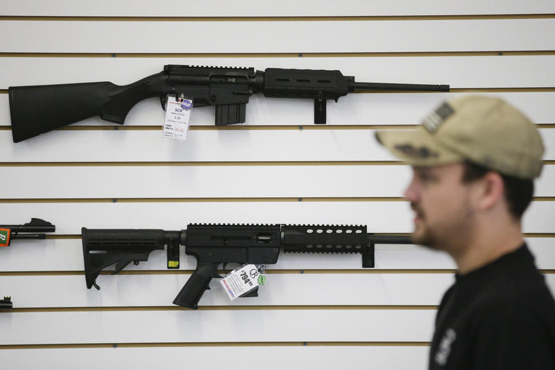 In this Dec. 9, 2015, photo, a sales associate walks past semiautomatic rifles at Bullseye Sport gun shop in Riverside, Calif.