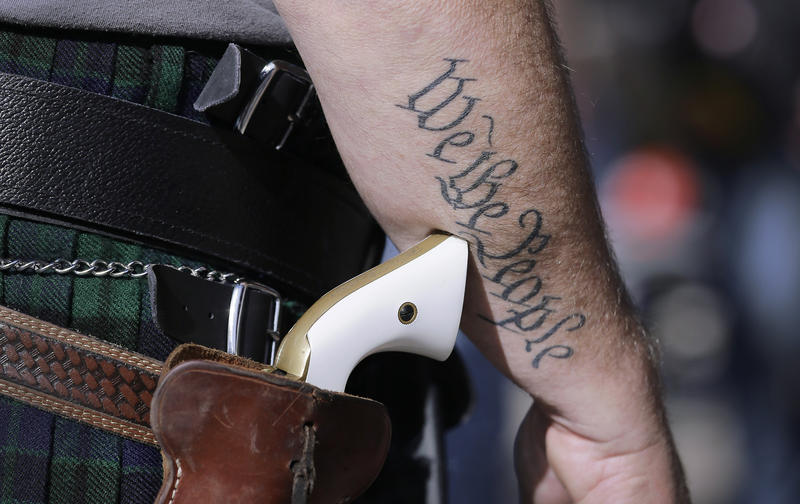 In this Jan. 26, 2015, file photo, Scott Smith, a supporter of open carry gun laws, wears a pistol as he prepares for a rally in support of open carry gun laws at the Capitol, in Austin, Texas.