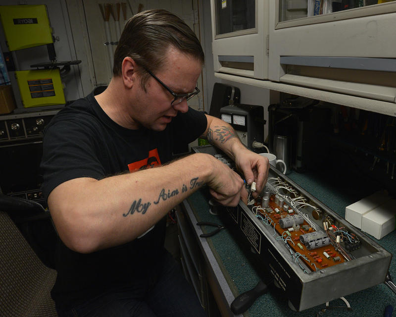 Tannar Brewer repairs electronics on an amplifier in a north Seattle workshop. Brewer is a partner in an instrument repair business with Chris Lomba.