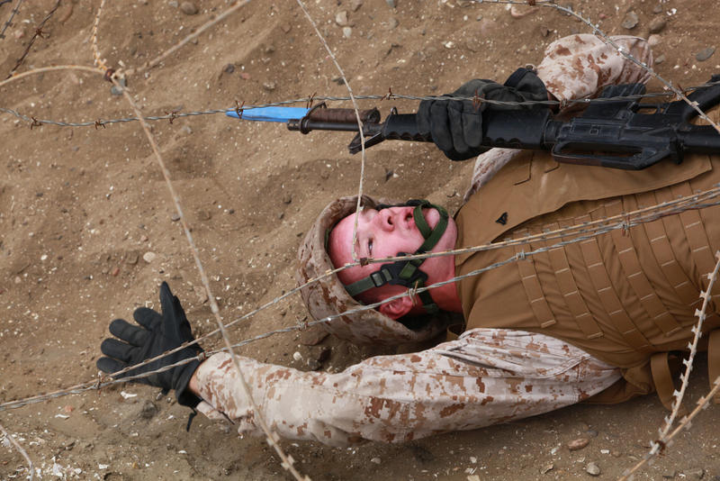 A U.S. Marine, with Headquarters and Headquarters Squadron, navigates under constantina wire during a bayonet course training evolution aboard Marine Corps Recruit Depot, San Diego, Calif., June 1, 2012.