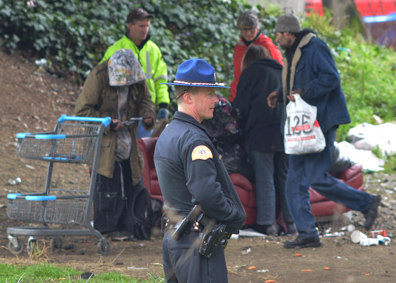 A Washington State Patrol trooper looks on as a homeless camp is cleaned out at the corner of Airport Way South and South Royal Brougham Way on Wednesday, January 27, 2016. That's a short way from where two people were shot to death in 'The Jungle.'