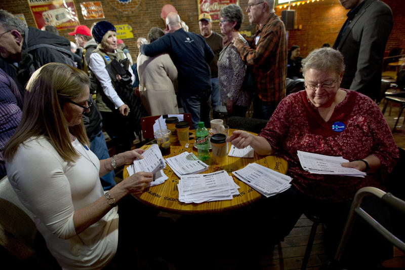 In this Jan. 25, 2016, photo, volunteers sort through commitment to caucus for Democratic presidential candidate Hillary Clinton cards during a campaign event at the Smokey Row in Oskaloosa, Iowa.