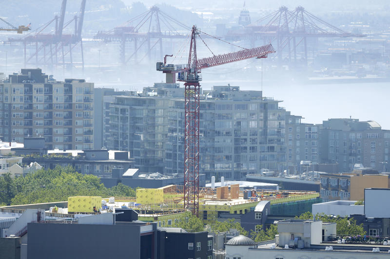 A construction crane working on a building is shown with Port of Seattle cranes in the background on a foggy summer day, Monday, July 15, 2014, in Seattle.