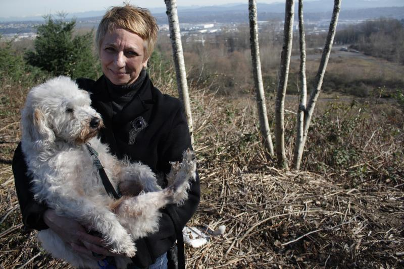 Barbara Dobkin, council of the North Highline Unincorporated Area Council, stands with her dog Mattie on a hill in front of the Seattle city-owned land she'd like to see turned into a park.