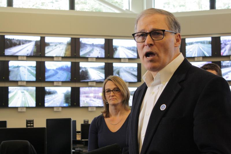 Washington Governor Jay Inslee stands before a wall of traffic monitors at a state transportation management center with Patty Rubstello, WSDOT's Assistant Secretary for Tolling