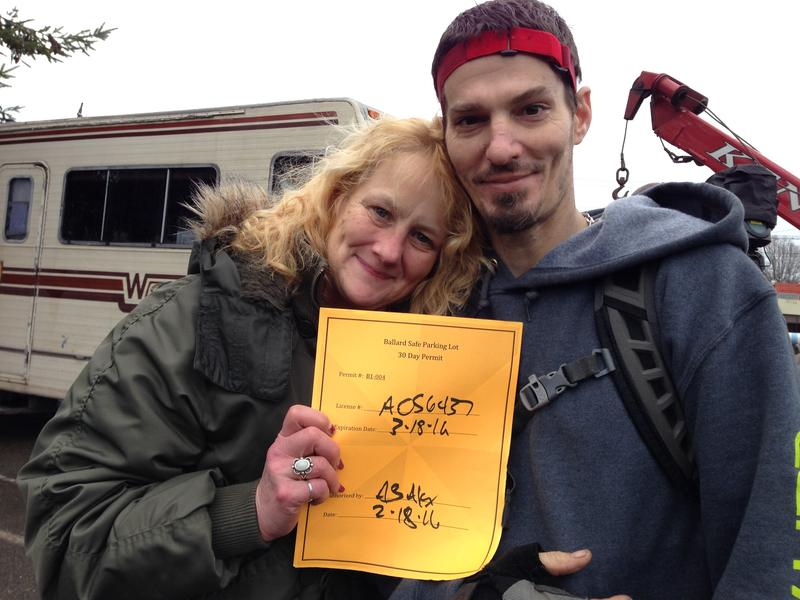 Wanda Williams, a former nurse who has been homeless for three years, and her roommate Tim Pugsley hold up a permit that allows them to stay in Seattle's RV Safe Lot in Ballard.