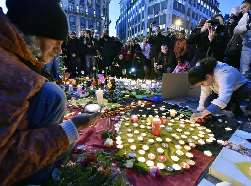 People bring flowers and candles to mourn for the victims at Place de la Bourse in the center of Brussels, Tuesday, March 22, 2016.