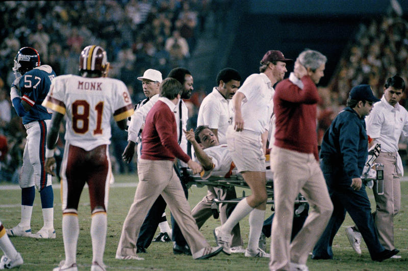 Washington Redskins quarterback Joe Theismann gestures as he is carried off the field at RFK Stadium in Washington, D.C., Nov. 18, 1985. Theismann injured his right leg during second quarter action.
