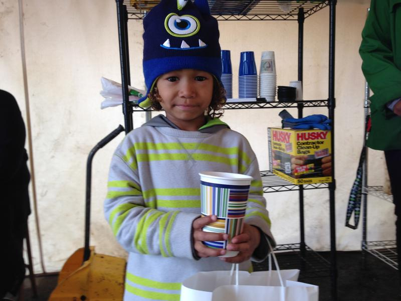 Five-year-old Tiui gets a snack from the makeshift pantry in Othello Village, the newest honeless encampment in southeast Seattle
