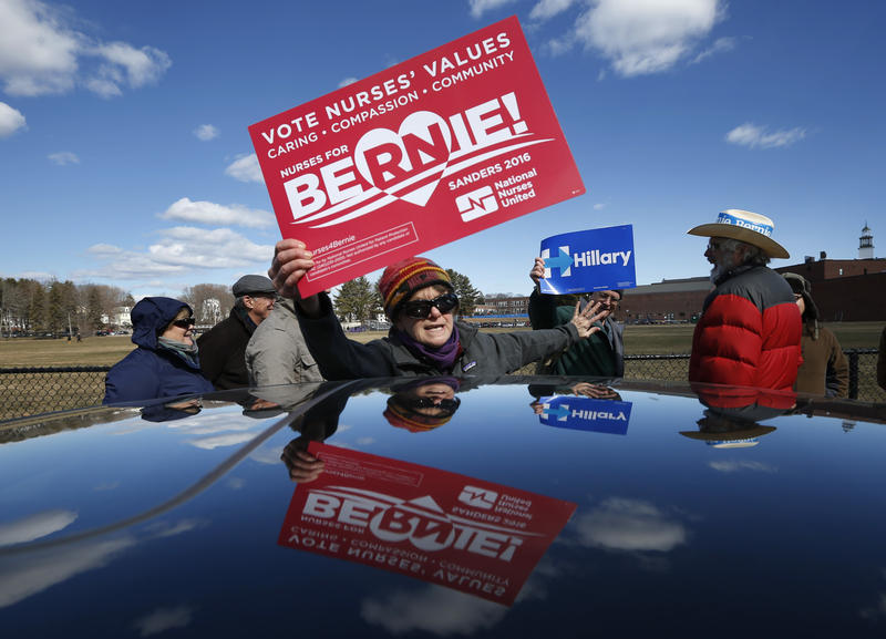 Claudine Weatherford of Peaks Island, Maine, shows her support for Democratic presidential candidate Bernie Sanders as she tries to block her brother-in-law, Jeremy Wyant, a Hillary Clinton backer, while waiting in line at a Democratic caucus on Sunday.