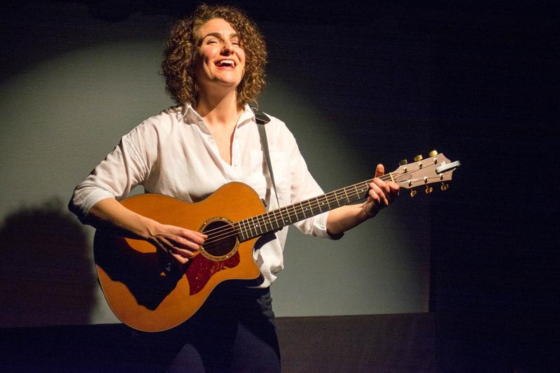 Bridget Quigg plays guitar on stage during her one-woman show 'Techlandia.'