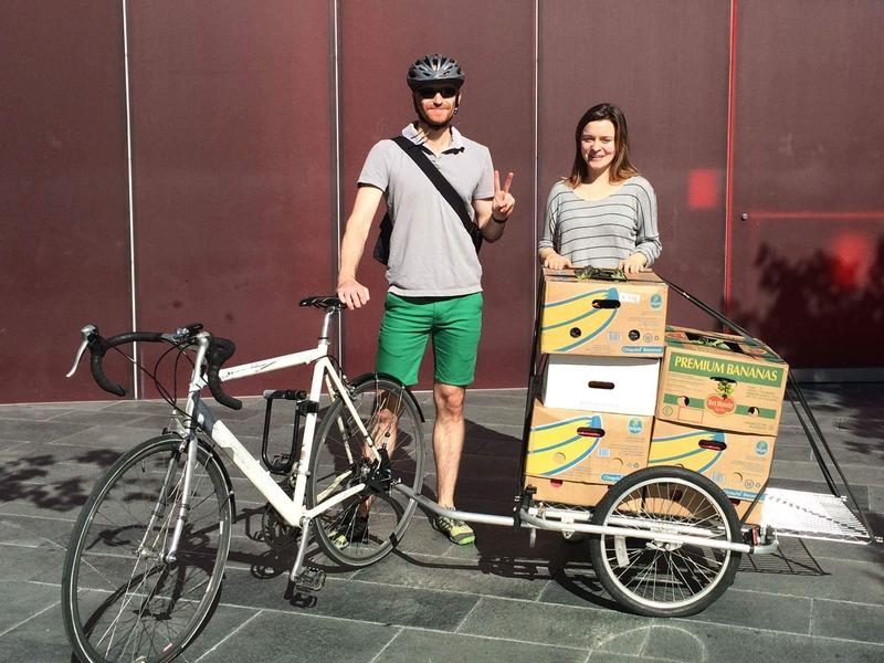 Seattle Food Rescue volunteer Caz VanDevere on the left stands with his bike along with Laura Graber from the Pike Market Food Bank.