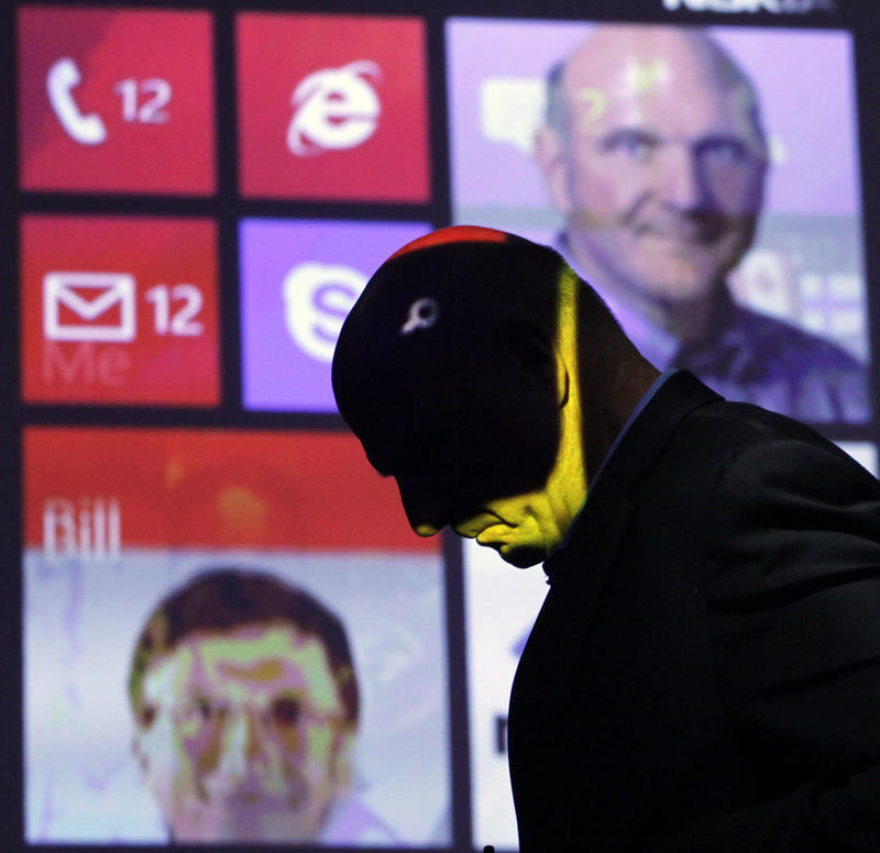 Steve Ballmer, former CEO of Microsoft, walks past a projected display showing Bill Gates, lower left, and himself, during a discussion of Nokia's Lumia 920, equipped with Microsoft's Windows Phone 8, Sept. 5, 2012 in New York.