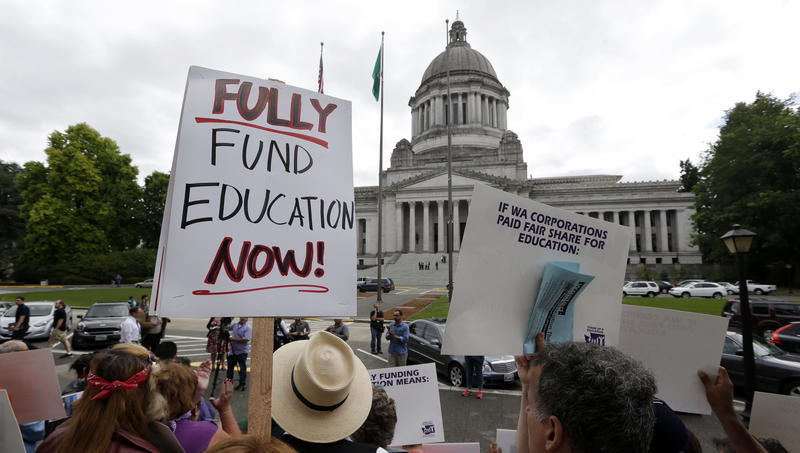 Demonstrators on the steps of the Temple of Justice advocate for more state spending on education, Sept. 3, 2014, in Olympia. The court ordered lawmakers to explain why they haven't followed its orders to fix the way Washington pays for public education.