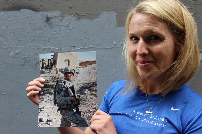 Lisa Hallett holding a photo of her husband John