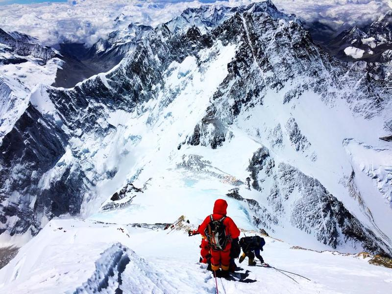 Climbers descend Mount Everest in good weather.