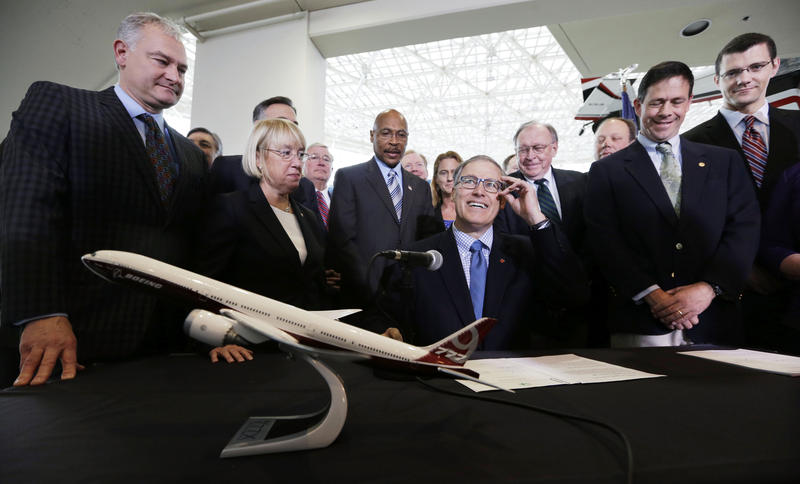 In this Nov. 11, 2013 file photo Washington Gov. Jay Inslee, center, adjusts his glasses as he prepares to sign legislation in Seattle to help keep production of Boeing's new 777X in Washington.