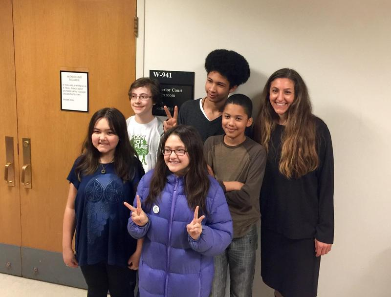 Aji Piper (top row, middle) Adonis Piper (second row, right) and attorney Andrea Rodgers (top row, right) at King County Superior Court, outside the courtroom where they won their case.
