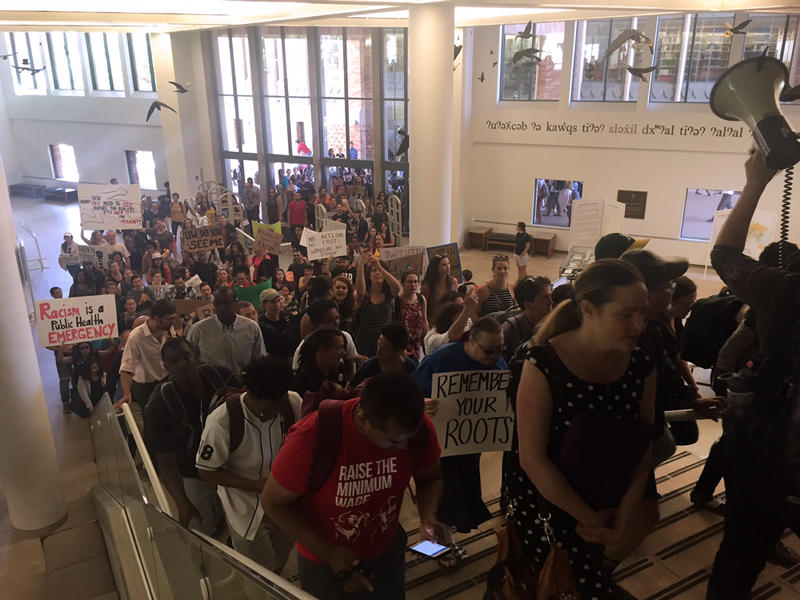 Students and staff march through Suzallo Library during a walkout on Thursday, May 12, 2016, to protest racial inequity on campus.