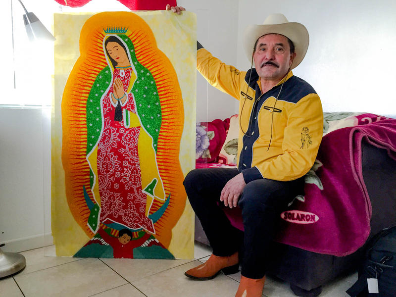 Francisco Hernandez poses with his beaded Virgin of Guadalupe in his White Center apartment