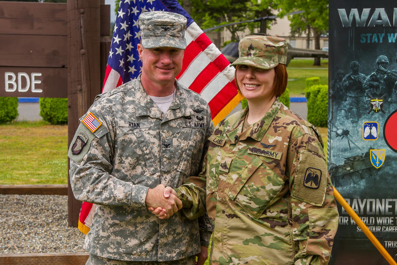 U.S. Army Soldiers assigned to 16th Combat Aviation Brigade, 7th Infantry Division come together for the first reenlistment of cavalry scout Kayci Landes in the Army at JBLM on May 4.
