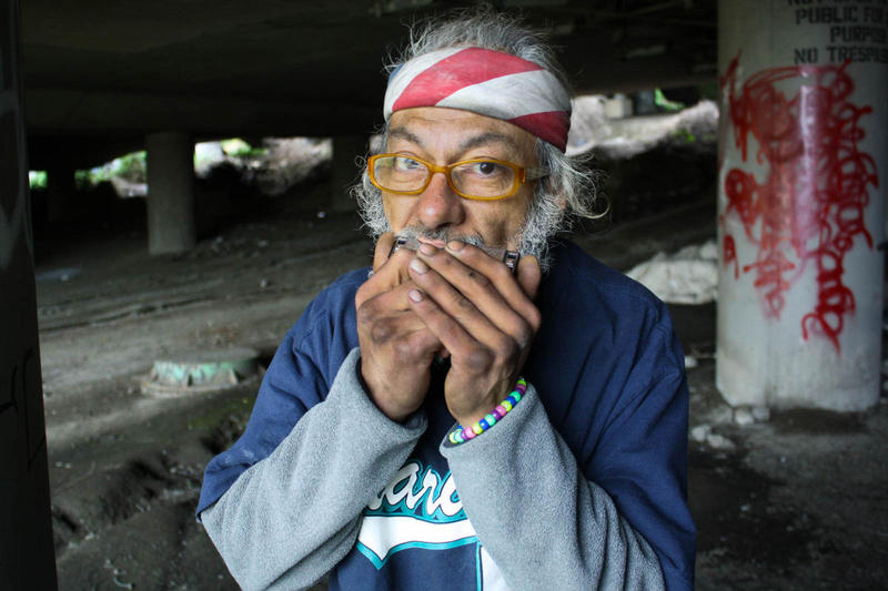 Jacobo Miguel Pinon Jr. plays the harmonica at his space in the Jungle, a homeless encampment that houses more than 400 people by some estimates.