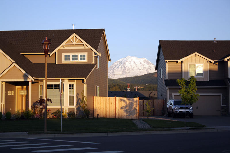 Mt. Rainier peeks between two houses in Orting, Washington.
