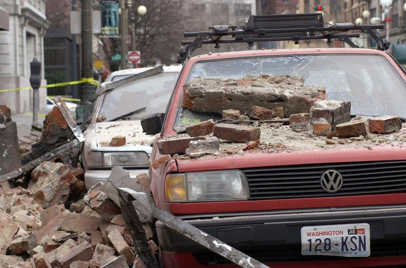 Bricks that fell from an earthquake cover parked cars in Seattle's Pioneer Square district, Wednesday, Feb. 28, 2001 after a magnitude 6.8 earthquake which damaging buildings and roads, and closing Seattle's two airports.