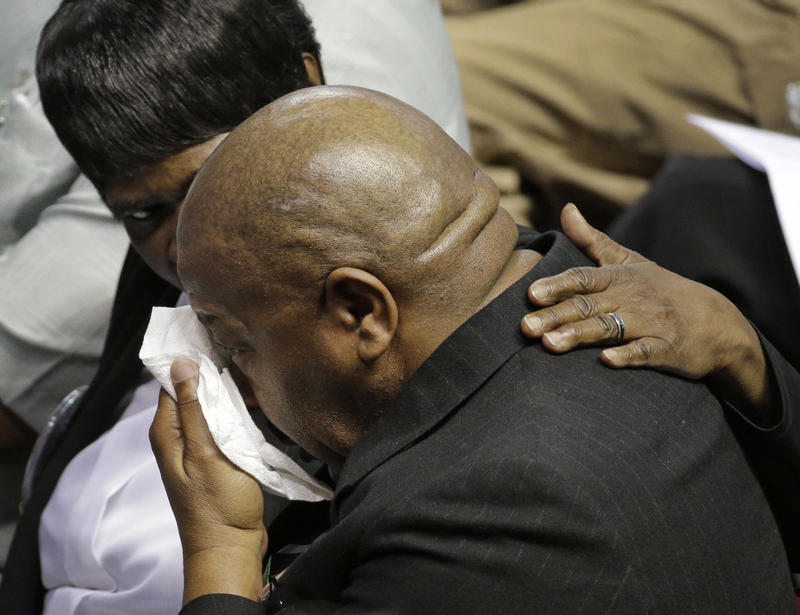 A mourner is comforted during a memorial in Charleston, S.C., Friday, June 17, 2016 on the anniversary of the killing of nine black parishioners during bible study at Mother Emanuel AME Church.