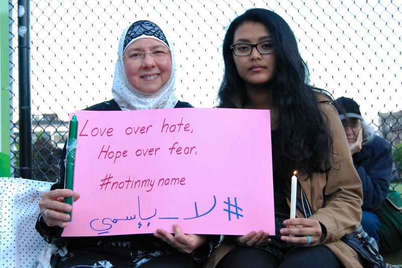 Aishah Jilani, left, wrote the hashtag #notinmyname in Arabic during a vigil at Cal Anderson Park for the victims of the Orlando shooting.