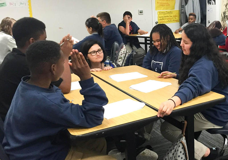 At Excel Public Charter School in Kent, Academic Intervention Specialist Mona Swanson works with students in a science class.