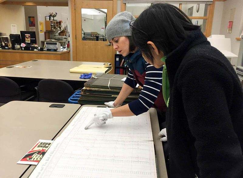 Online editor Isolde Raftery reads an old residential ledger at the Puget Sound Regional Branch of the Washington State Archives in Bellevue.