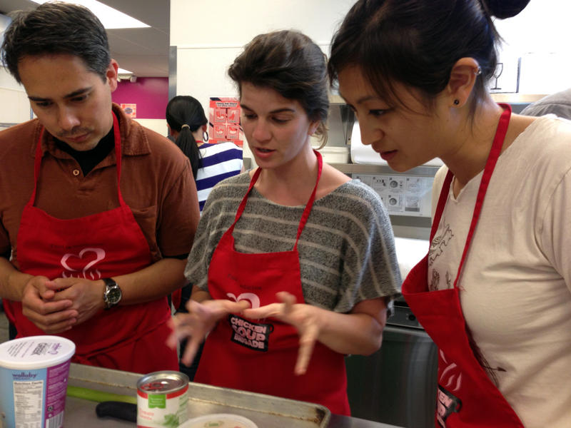 Medical residents Bryn Chowchuvech, Bari Laskow and Stephanie Ngo discuss strategy for making their spaghetti dish.