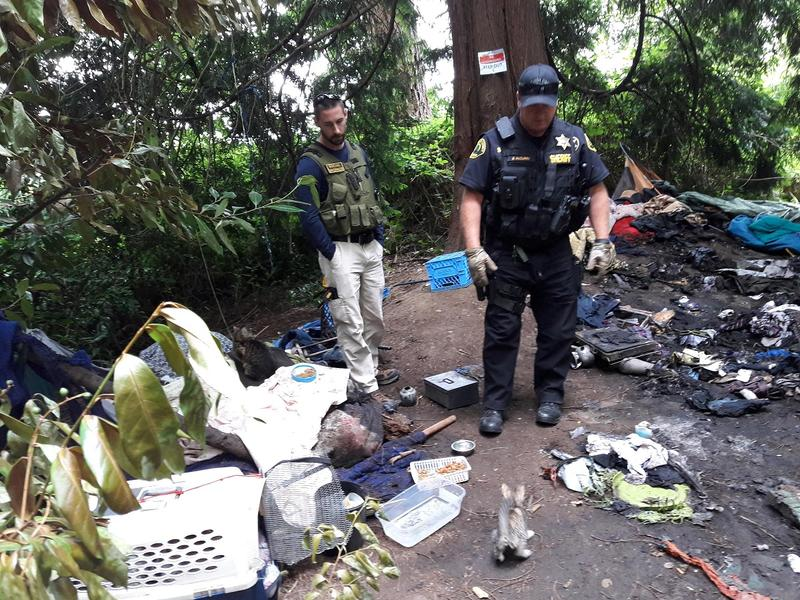 Jesse Calliham, left, and Deputy Bud McCurry survey the charred debris at a south Everett encampment.
