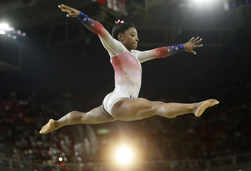 "Simone Biles, a 4'8"" package of muscle, performs at an Olympic exhibition gala after having won four gold medals and one bronze in the 2016 Games. What she is wearing is not relevant."