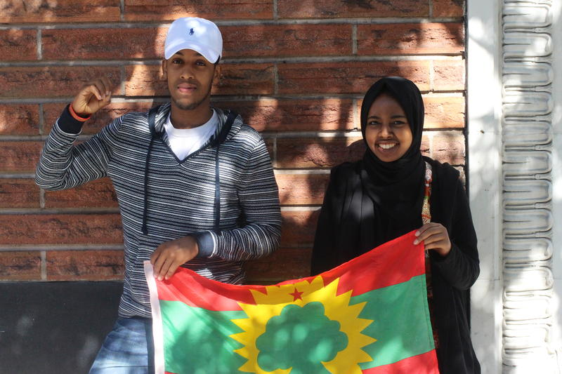 Hosts Awal Ibrahim and Zubeyda Ahmed hold the Oromo flag.