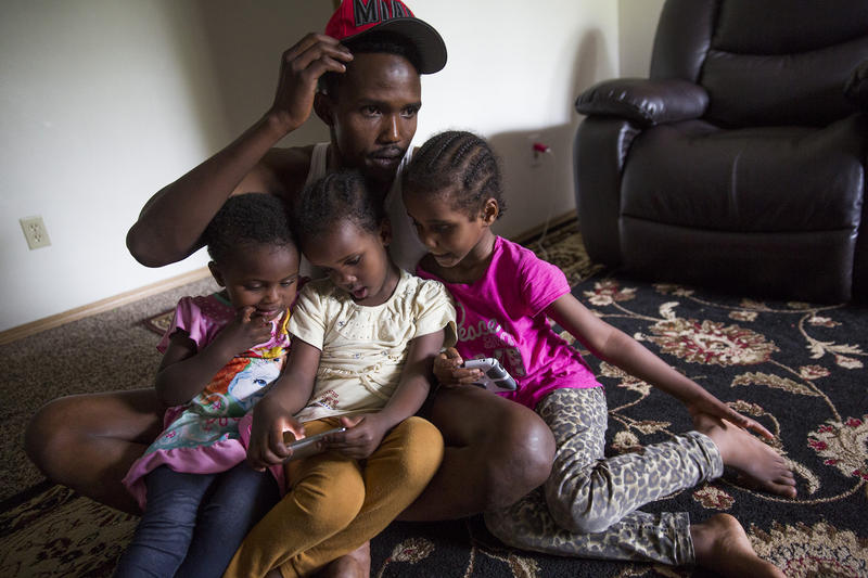 Osman Mohamed, of Somalia, and his three daughters, ages 2, 4 and 5. Osmon hoped to find paradise in Seattle, but in his first year, his family witnessed a shooting and he was hit by a car.