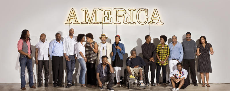 "Some of the artists represented in ""30 Americans"" pose beneath a neon artwork created by Glenn Ligon."