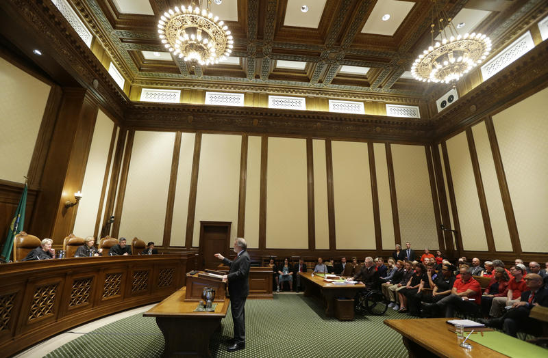Alan Copsey, center, a deputy attorney general for the state of Washington, speaks during a hearing before the Washington State Supreme Court regarding a lawsuit against the state over education funding, Wednesday, Sept. 7, 2016, in Olympia, Wash.