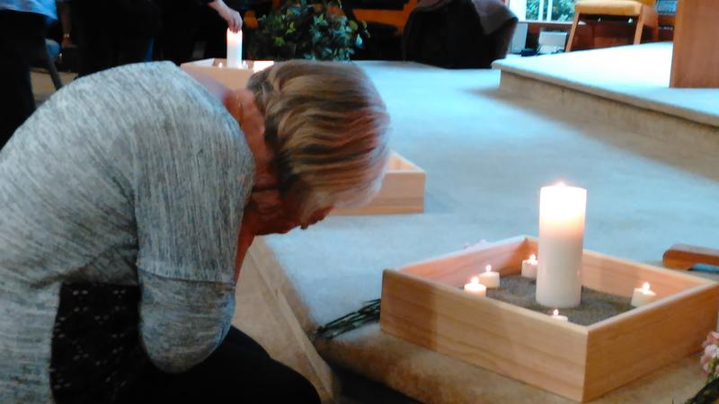 Community members light candles for the victims of the Cascade mall shooting