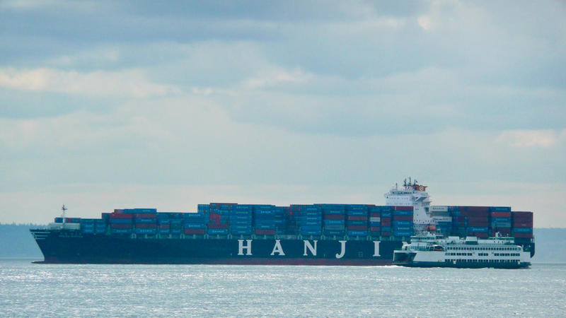 A Hanjin shipping container ship dwarfs a Washington State Ferry.
