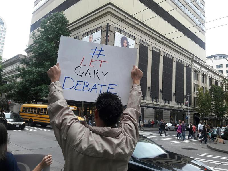Trifin Sergieff of Des Moines, Washington, held the sign. He says Johnson's message in debate would be less war, and lower taxes.