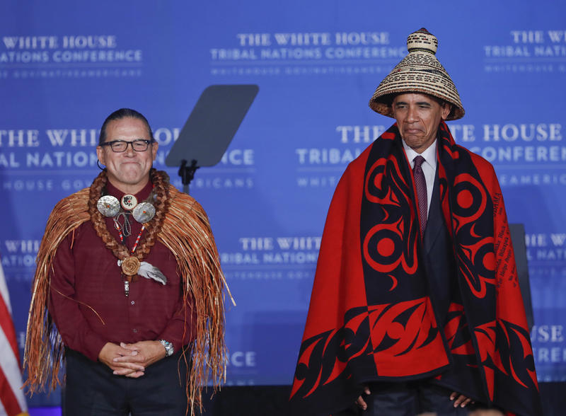 President Barack Obama wears a blanket and hat given to him by Brian Cladoosby, left, President of National Congress of American Indians, during the 2016 White House Tribal Nations Conference, Monday, Set. 26, 2016.