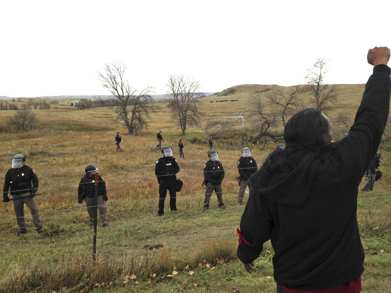 A Dakota Access pipeline protester defies law enforcement officers who are trying to force them from a camp on private land in the path of pipeline construction, Thursday, Oct. 27, 2016 near Cannon Ball, N.D.