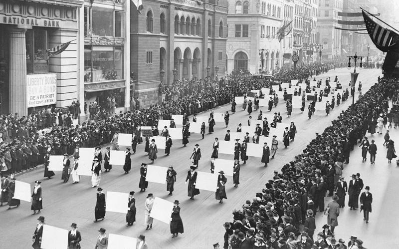 Women's suffragists parade in New York City in 1917, carrying placards with signatures of more than a million women.