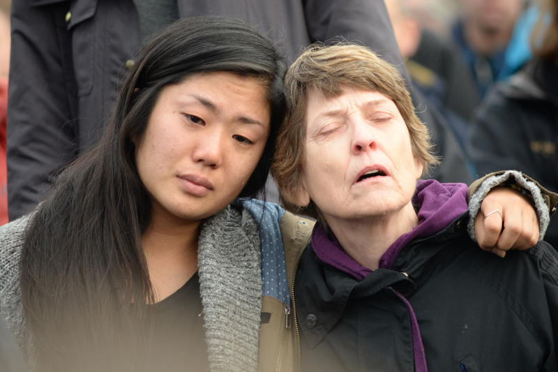 "Hannah Atlas hugs her mom, Judith Gille, as the crowd sings the late Leonard Cohen's ""Hallelujah"" during a vigil Sunday at Seattle's Cal Anderson Park."