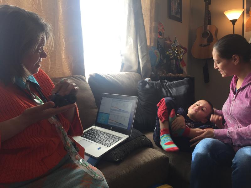 GLEA family advocate Camille Churchill visits with four-year-old Moise, and his mother, Angela Madrid