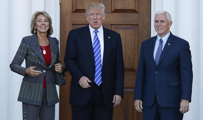 President-elect Donald Trump calls out to media as he Vice President-elect Mike Pence and Betsy DeVos pose for photographs at Trump National Golf Club Bedminster clubhouse in Bedminster, N.J., Saturday, Nov. 19, 2016.