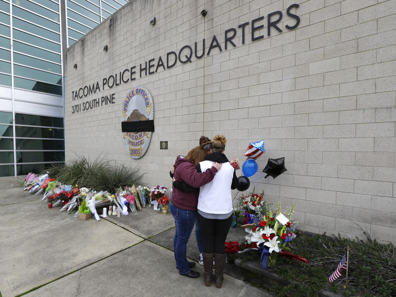 Three women embrace as they stand at a growing memorial, Thursday, Dec. 1, 2016, at Tacoma Police Department headquarters in Tacoma, Wash. A Tacoma Police officer died Wednesday night at a hospital after being shot multiple times earlier in the day.